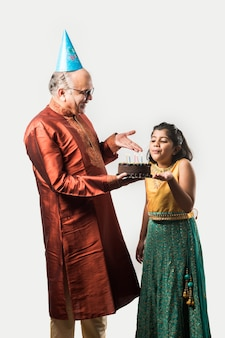 Indien senior ou vieil homme avec sa petite-fille célébrant son anniversaire en soufflant des bougies sur un gâteau tout en portant des vêtements ethniques, debout isolé sur fond blanc