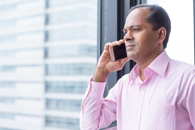 Un indien sérieux parlant au téléphone à la fenêtre