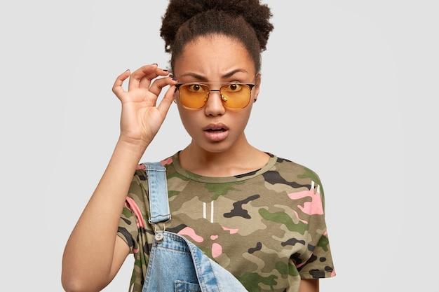 Indignée jeune femme noire regarde avec perplexité à travers les nuances