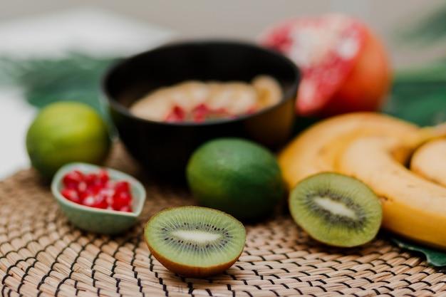 Les indispensables pour cuisiner un bol de smoothie. assiette blake garnie de kiwi, banane, graines de grenade, citron vert, granola, graines de chia. petit-déjeuner sain. ambiance tropicale.
