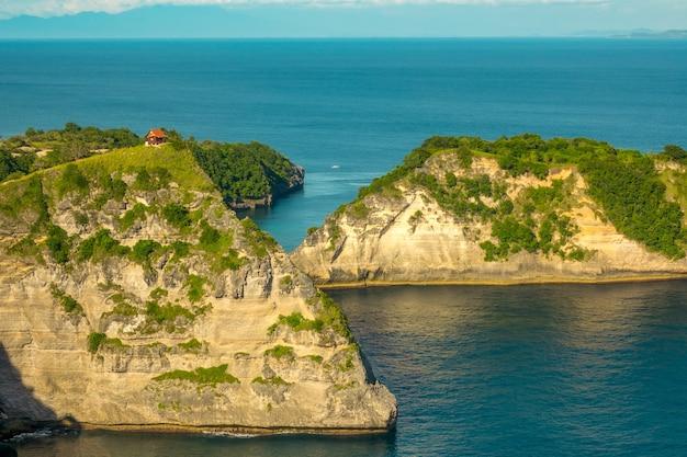 Indonésie. côte rocheuse d'une île tropicale. petite maison au sommet de la montagne. végétation luxuriante et eau turquoise de l'océan