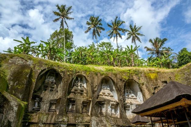 Indonésie. île de bali. temple creusé dans la roche, toits de chaume et palmiers sur fond de ciel