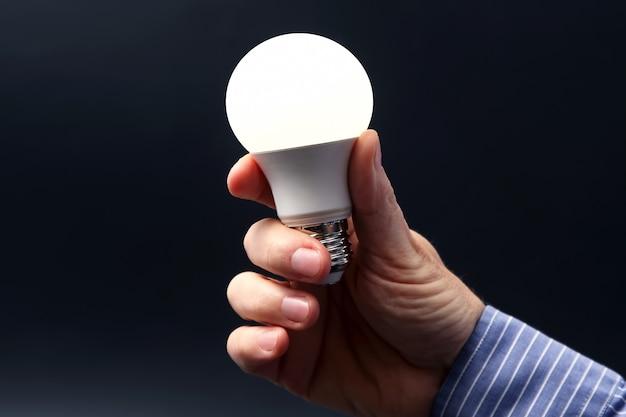 Industrie industrielle électrique. inclus une nouvelle lampe à led dans la main humaine sur l'obscurité