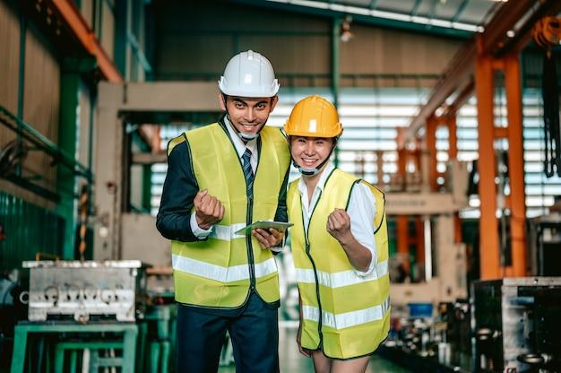 Industrie de l'ingénieur femme asiatique portant un casque et tenant une liste de contrôle debout dans la zone de la machine