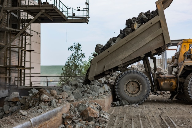 Industrie minière: un camion à benne basculante lourd décharge du granit dans un énorme concasseur de pierres