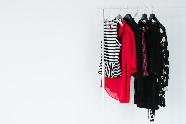 Industrie de la mode et conception de vêtements. nouvelle collection de vêtements. sélection de vêtements lumineux suspendus sur le support.