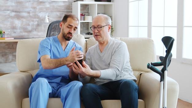 Un infirmier aide un vieil homme à la retraite à utiliser un smartphone dans une maison de retraite lumineuse et confortable