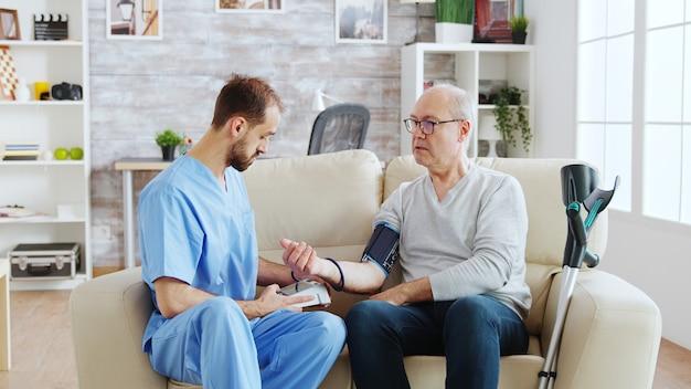 Infirmier mesurant la tension artérielle d'un homme retraité dans une maison de retraite lumineuse et confortable