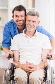 Infirmier parlant avec un patient senior en fauteuil roulant.