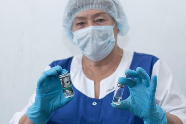 Une infirmière âgée tient une seringue et une ampoule