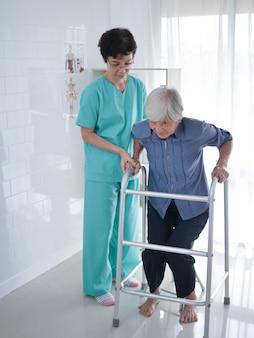 Infirmière aidant une femme âgée à l'aide de cadre de marche.