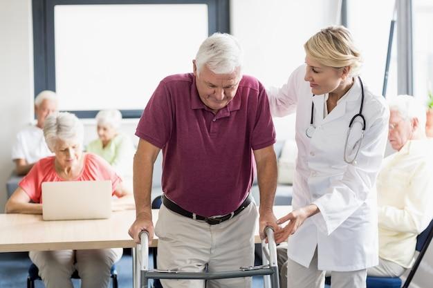 Infirmière aidant senior avec aide à la marche