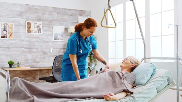 Infirmière aidant une vieille femme handicapée et retraitée à se coucher. le soignant la couvre d'une couverture.
