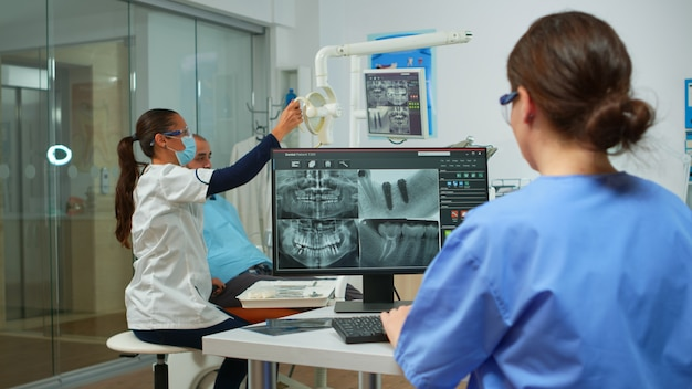 Infirmière analysant la radiographie numérique assise devant un ordinateur dans une clinique de stomatologie, tandis qu'un médecin avec un masque facial travaille avec un patient en arrière-plan examinant les problèmes de dents, allumant la lampe