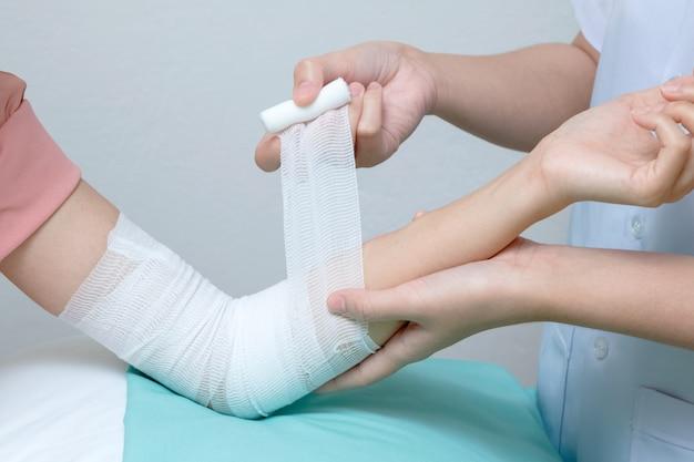 Infirmière appliquant un bandage au patient blessé au coude