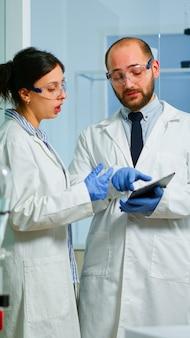 Infirmière chimiste expliquant au médecin le développement de vaccins dans un laboratoire moderne équipé pointant sur une tablette. équipe de médecins examinant l'évolution du virus à l'aide d'un diagnostic de recherche de haute technologie