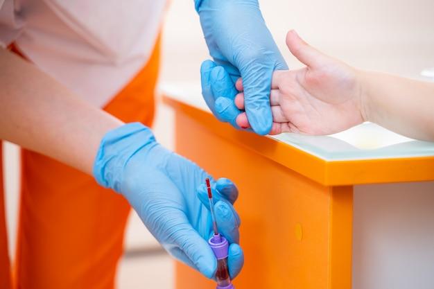 Infirmière collecte un échantillon de sang d'un doigt