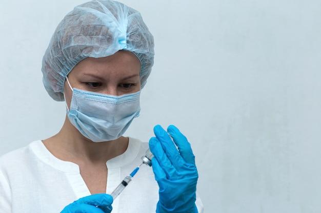 Une infirmière compose l'injection dans la seringue, la vaccination