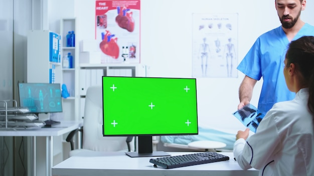 Infirmière consultant un médecin dans une armoire d'hôpital tout en travaillant sur un ordinateur avec un écran vert d'espace de copie disponible. bureau avec écran remplaçable dans une clinique médicale pendant que le médecin vérifie le patient ra