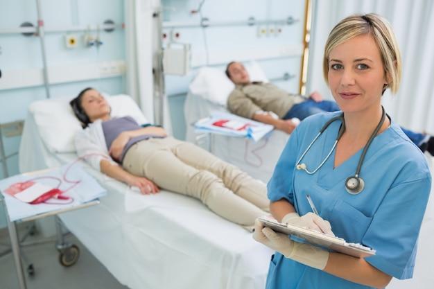 Infirmière à côté des patients transfusés écrivant sur un presse-papiers