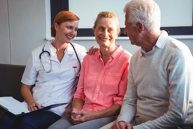 Infirmière et couple de personnes âgées assis sur un canapé