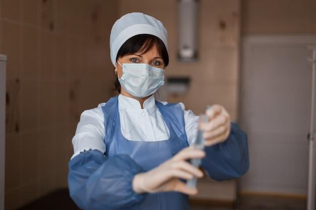 L'infirmière dans un masque protecteur en tenue médicale est debout, tenant une seringue à la main. infirmière se prépare pour le vaccin contre la grippe