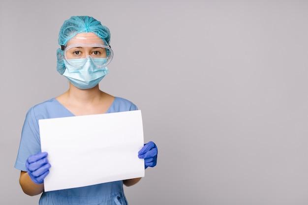 Une infirmière dans un uniforme de protection médicale détient une feuille blanche vierge sur un fond gris isolé soins de santé