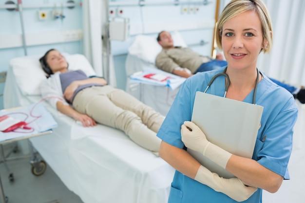 Infirmière debout à côté des patients transfusés