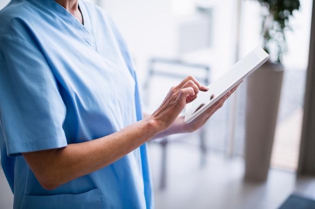 Infirmière, debout, hôpital, couloir, utilisation, tablette numérique
