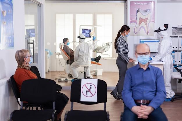 Infirmière-dentiste vêtue d'un costume ppe avec le visage shiled discutant avec le patient dans la salle d'attente de stomatologie