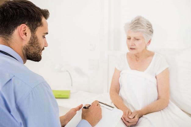 Infirmière à domicile écoutant une femme âgée et écrivant dans le presse-papiers de la chambre