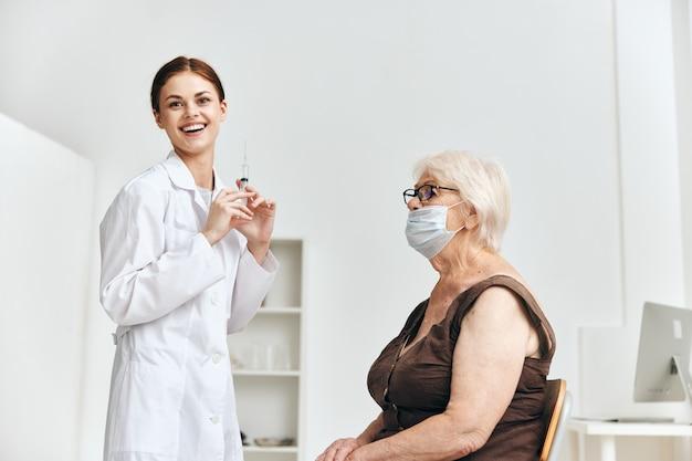 Infirmière donnant l'injection à un hôpital de vaccination de femme âgée