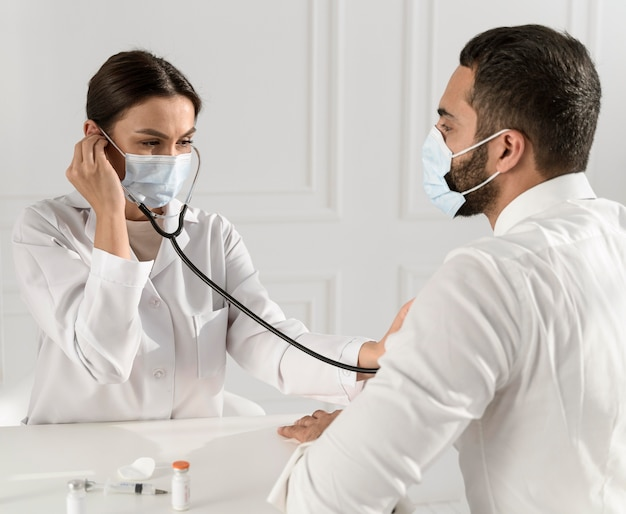 Infirmière à l'écoute du rythme cardiaque de l'homme