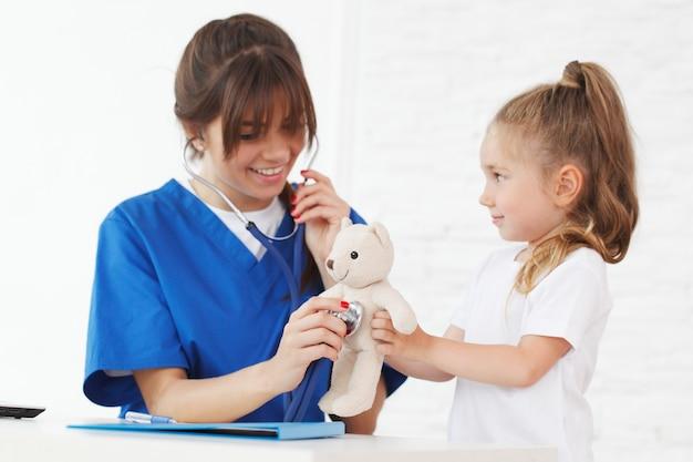 Infirmière et enfant examinant l'ours en peluche