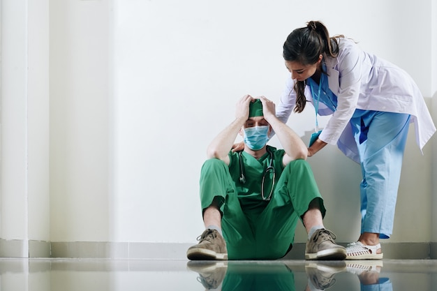 Infirmière essayant de rassurer un jeune chirurgien stressé assis sur le sol dans le couloir de la clinique après la mort du patient