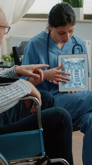 Infirmière expliquant l'ostéopathie aux rayons x sur tablette à l'homme