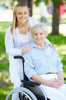 Infirmière avec une femme âgée en fauteuil roulant