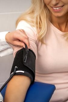 Infirmière ou femme médecin met le tonomètre sur le bras de la jeune femme à l'hôpital