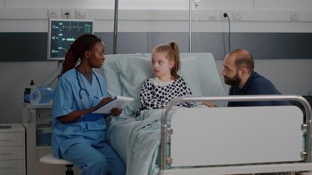 Infirmière de femme pédiatre afro-américaine expliquant le traitement des soins de santé