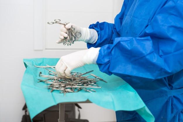 Infirmière de gommage préparant des instruments médicaux pour l'opération