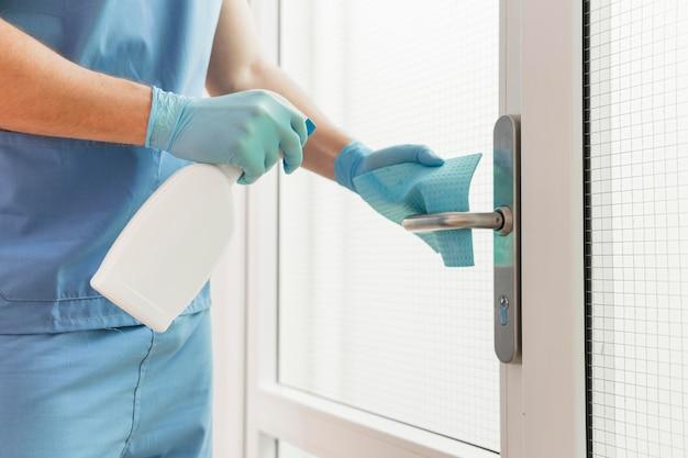 Infirmière en gros plan désinfectant la poignée de porte