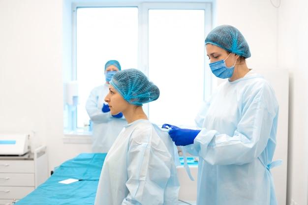 Une infirmière habille un chirurgien dans un costume stérile avant la chirurgie