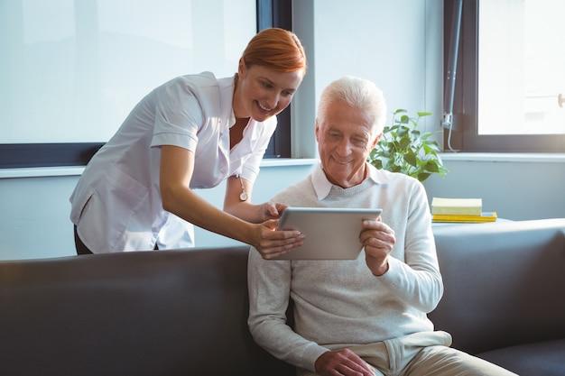 Infirmière et homme senior à l'aide d'une tablette numérique