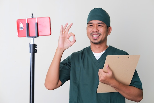 Infirmière de l'hôpital de sexe masculin donnant un signe ok au patient lors d'une consultation en ligne à l'aide d'un appel vidéo sur téléphone portable