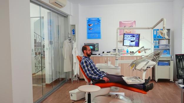 Infirmière invitant le prochain patient dans la salle de stomatologie montrant s'allonger sur une chaise. assistant dentaire assis dans une salle dentaire de consultation moderne avec un homme en attente d'un médecin dentiste spécialiste.
