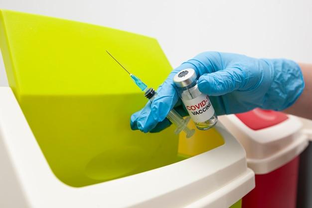 L'infirmière jette une seringue usagée, une bouteille de vaccin covid