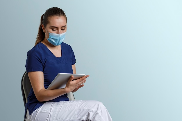 Infirmière latina avec masque assis travaillant avec tablette numérique
