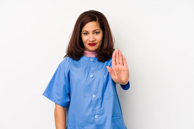 Infirmière latine d'âge moyen femme isolée debout avec la main tendue montrant le panneau d'arrêt