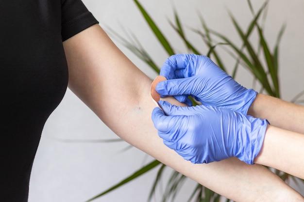 Infirmière ou médecin en gants de protection en caoutchouc bleu mettant un bandage adhésif sur le bras de la jeune femme après l'injection du vaccin