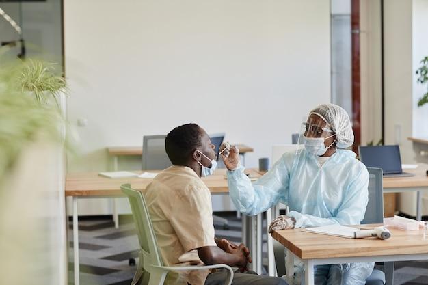 Infirmière médicale en costume d'epi expliquant à la patiente comment elle obtiendra un échantillon pour les tests de coronavirus